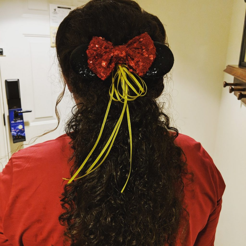 An intricate low ponytail with a special Mickey bow for a Gaston inspired Disney Character Couture makeover