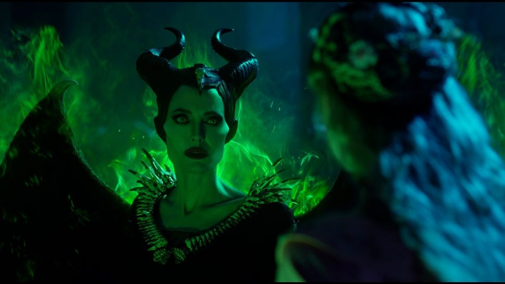 Maleficent glowing green from her powers as Aurora tries to calm her.
