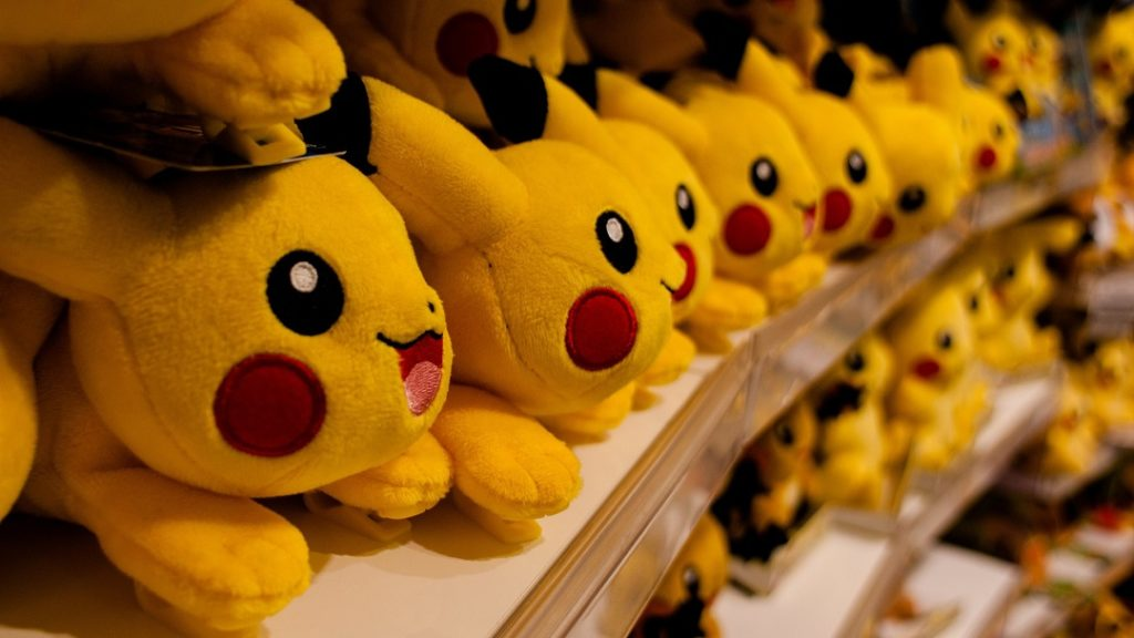 Row of Pokemon Pikachu stuffed animals in store.