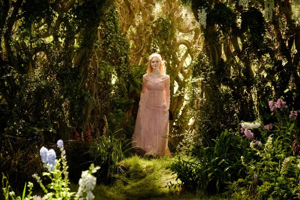 Aurora (Elle Fanning) walking in the moors.