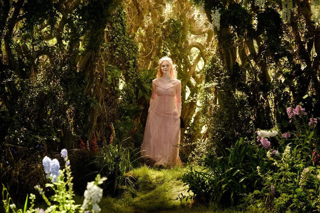 Aurora (Elle Fanning) walking in the moors.