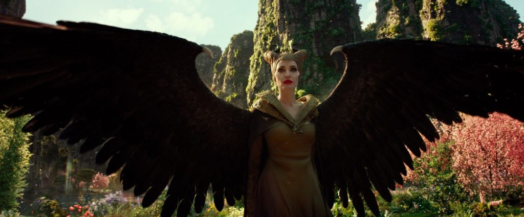 Maleficent (Angelina Jolie) with her wings spread wide in the moors.