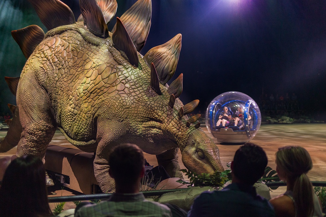 Scene from Jurassic World Live Tour featuring a Stegosaurus and Gyrosphere.
