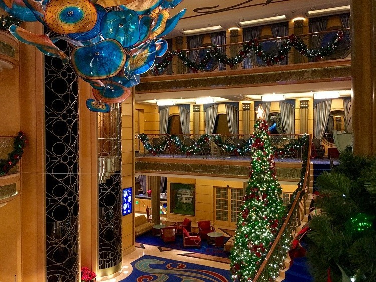 A Disney Cruise ship decorated for Christmas with a tree, lights and garland.