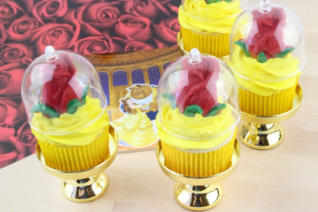 Beauty and the Beast cupcakes finished product is a yellow frosted cupcakes with a red chocolate rose