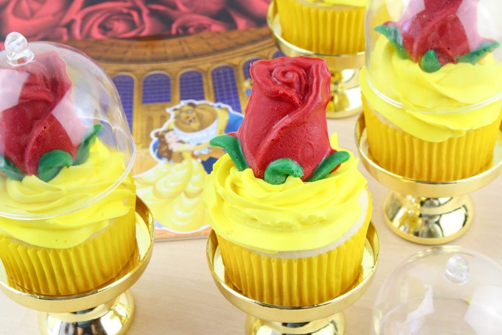 Beauty and the Beast cupcakes are a white cupcake with yellow frosting and a red chocolate rose.