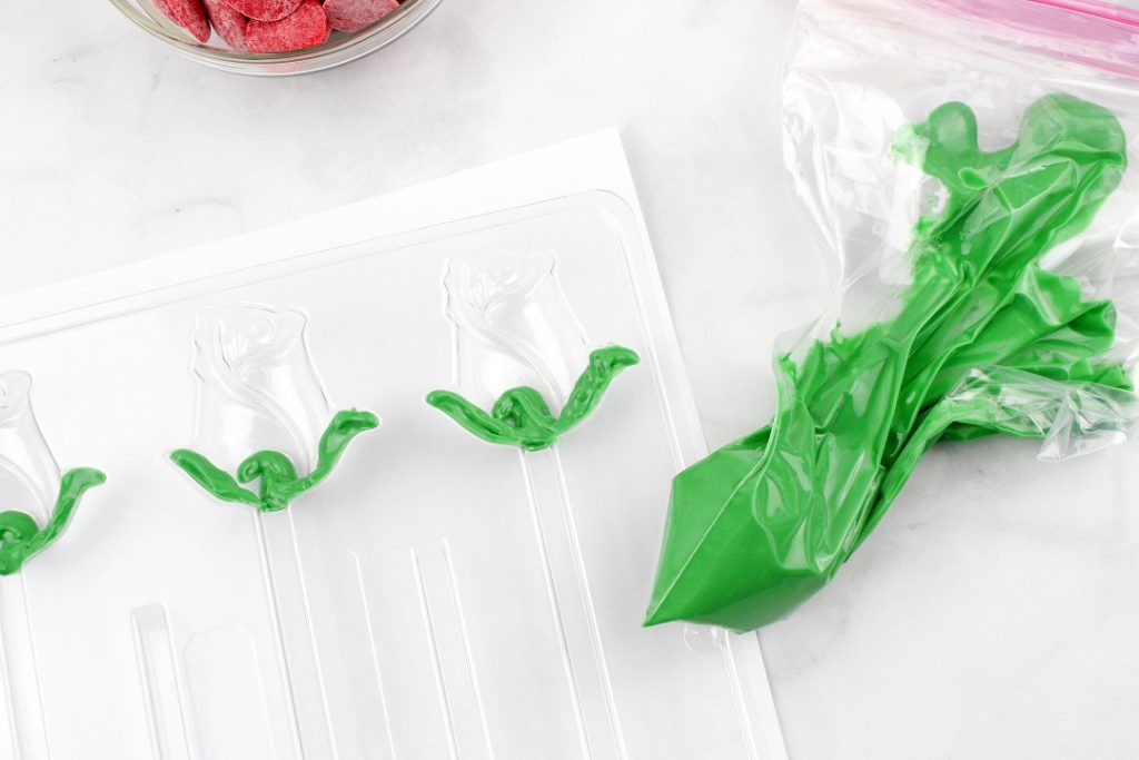 Melted green chocolate melts in baggie filling in the leaves of a rose candy mold.
