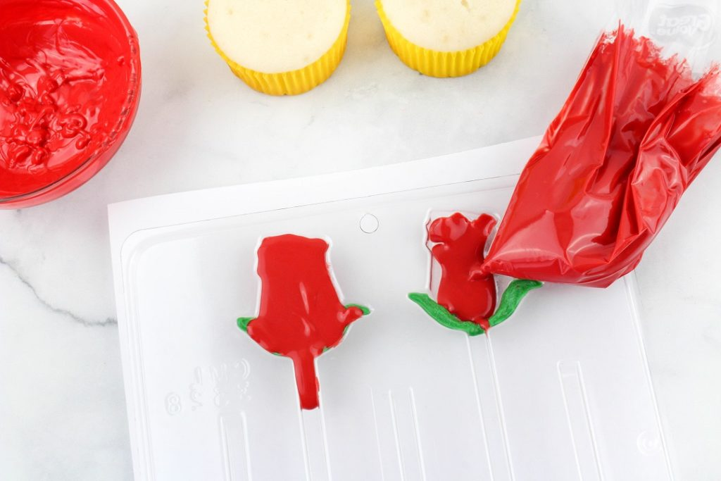 Red chocolate candy melts melted in a baggie filling in the rose candy mold.