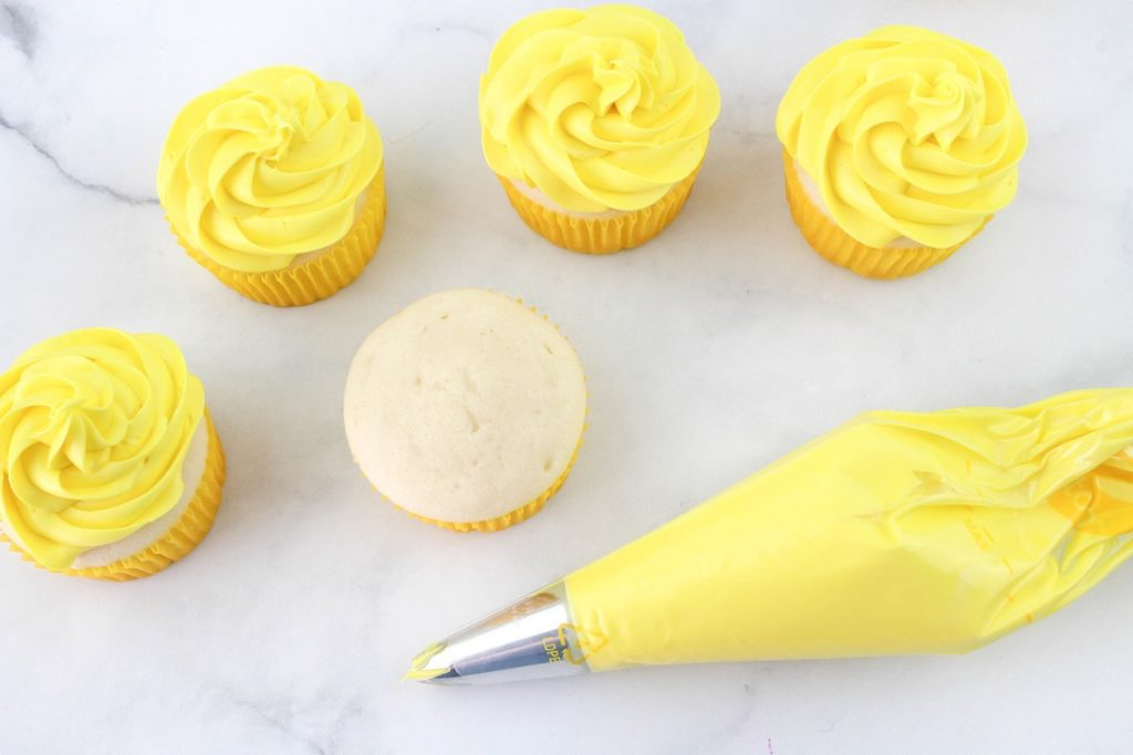 Yellow frosting in piping bag and 4 frosted cupcakes