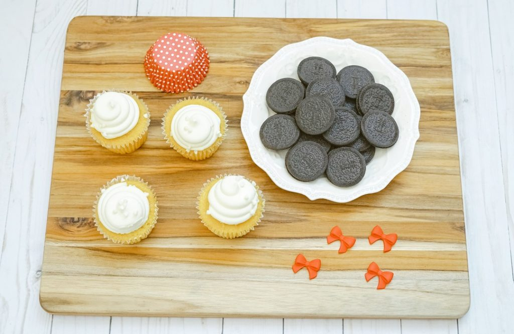 Frosted cupcakes, Oreo thin cookies and Wilton red candy bows are all you need to make Minnie Mouse cupcakes at home.