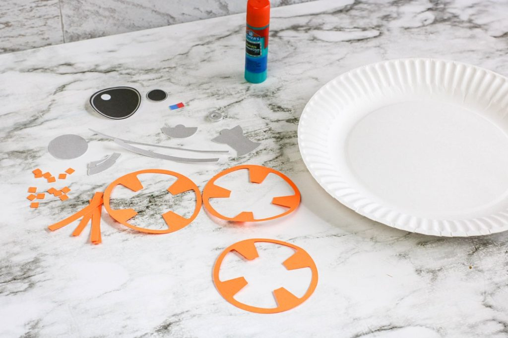Pieces cut out with a glue stick and paper plate ready to do the BB-8 paper plate craft.