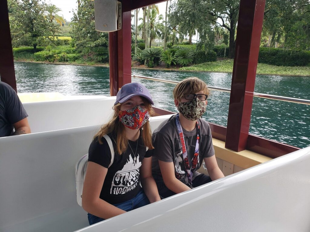 Girl and boy with cloth face masks on riding the water taxi at Universal Studios.