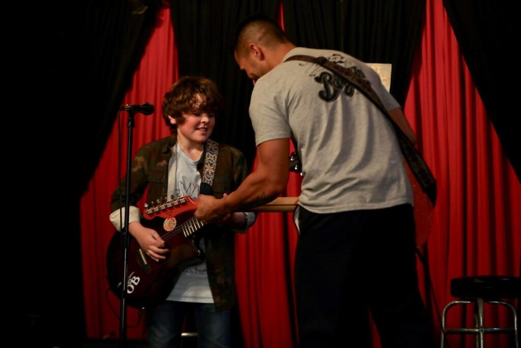 Oak Scoggins (Tommy Ragen) learning to play Vaughn's guitar with Pedro (Carlos Penavega).