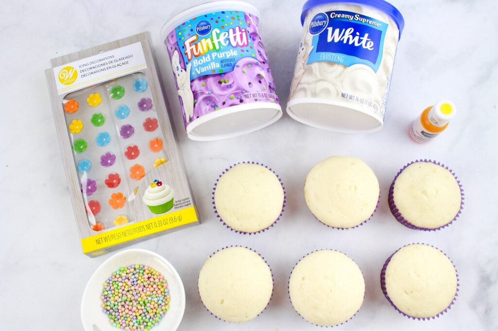 Ingredients for Disney inspired Rapunzel cupcakes: six cupcakes, purple and white frosting, yellow food coloring and Wilton candy flowers.